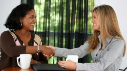 Two women shaking hands in an office, giving feedback